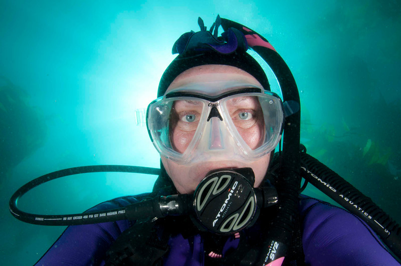 Nudi Head <br /> By Wendy Melill Taylor<br /> <br /> Photographer's notes:<br /> Hand held self portrait at Catalina Island wearing a Nudibranch cap. Many shots were taken by viewing my reflection in the dome port so that the sun was behind my head creating sun streaks, and positioning the dual strobes so they light my eyes within the mask without having the mask create shadows over the eyes. I had to hold my breath so that the bubbles disappeared.  After 22 years taking underwater photos, this is the first time I have turned the camera on myself. It was a good experience and took lots of adjustments of camera but mostly with my position in front of the dome port and with strobes.  Once I metered the background light the challenge was with bubbles, position in frame, strobe light position, strobe intensity and sun to subject.  It looks like a simple image but it is amazing what you have to deal with when underwater.  It was fun!