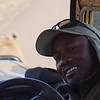 Trip Leader Joshua Lovuto posing with lion in front of vehicle - Serengeti