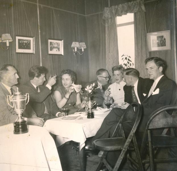 Albert Guðmundsson, knattspyrnumaður tók þátt í Meistaramóti GR árið 1954, en hann var þá í þann mund að ljúka ferli sínum sem atvinnuknattspyrnumaður. Hér sést hann, annar frá vinstri, lyfta glasi. Myndin er sennilega tekin á lokahófi Meistaramótsins í gamla golfskálanum.