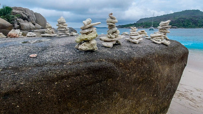 Cairns of coral on Cocos Island.  The Coryllis is in the backghround.