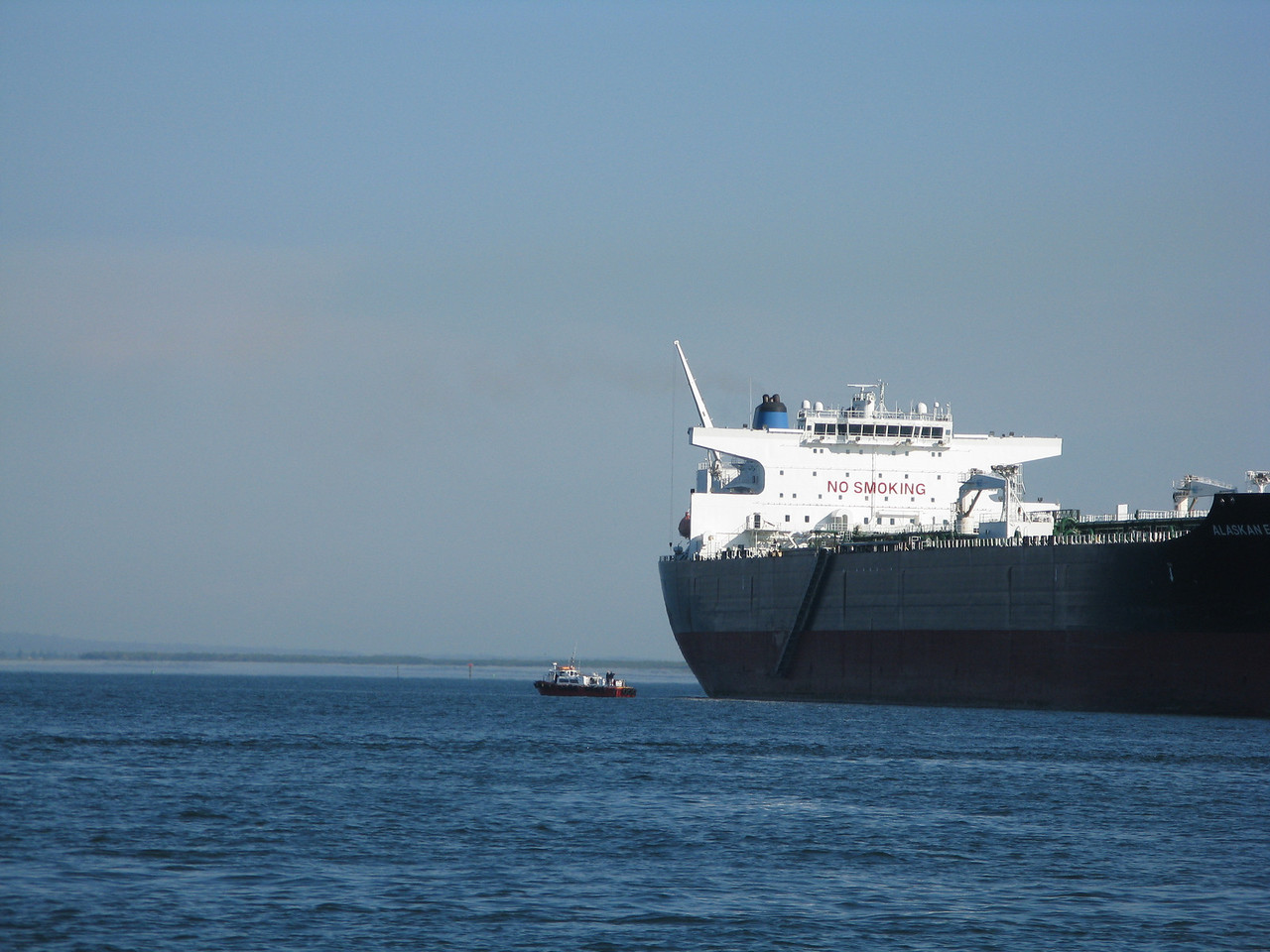 A pilot boat arrived at the oil tanker.   The pilot is a captain who guides the ship safely out to the open ocean.