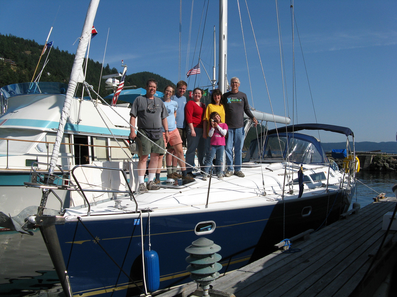 The crew on deck at Rosario Marina on Orcas Island..   (L to R) Martin, Ann, Nathan, Keegan, Sonia, Abby (in front) and Glenn.  The sailboat is a 40 foot Jeanneau named Salus rented from Anacortes Yacht Charters.