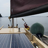 Making such slow progress in the tiny wind in the harbor that TB came out with his kayak and offered a tow!  Which worked!!  He towed AUKLET out to where you can see the wind riffling the water between those two points.  What a treat!<br /> <br /> Bonus in this photo is the picture of the solar panel – 55 watt eGanz.  This was a replacement for the similar output folding panel, which deteriorated after about two months of constant outdoor exposure – which, after all, it was not designed for!  The eGanz has worked out really well.  Also visible is the 12 foot push pole, stored to port on the cabin top.  Fantastic for getting off both rocks and sand bars!  Now how would I know that… Photo: Shemaya Laurel
