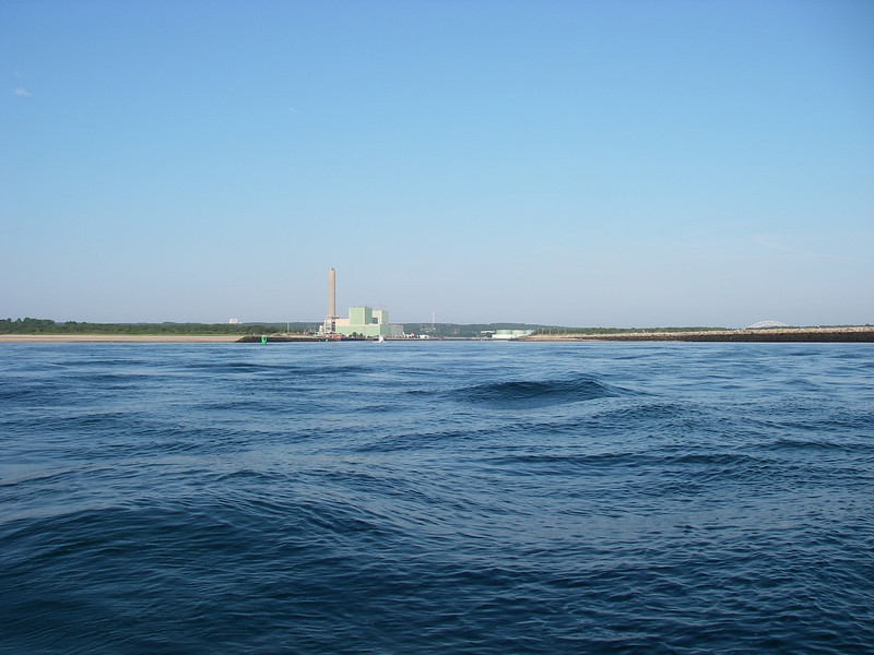 And this is what the canal entrance looks like, on the east end.  The stack is part of the big power plant – it comes in very handy from the far distance, finding your way back.  And the Sagamore Bridge is just visible a bit to the right, showing over the land.  July, 2012.
