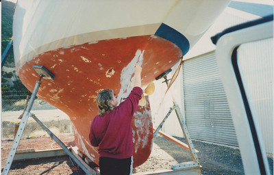 Undercoat going on.   Beautiful lines to the hull. This photo shows Al's wife Cheralyn applying Epiglass Marine Coat Primer to the hull, over the top of cured Evadure on the bare and feathered areas. The blue boot topping was being changed to Light Gull Grey to minimize sun absorption.