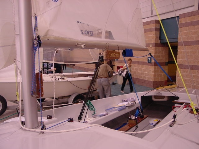 The Flying Scot mast is deck stepped.  For easy stepping a hinge pin is used at the base of the mast to hold the mast base in position as the mast is being raised.  The Outhaul and Cunningham control line shown with optional extra purchase for ease of trimming the Main sail.  Boom vang show with 6:1 purchase with control line lead back to the optional consol cleat on the centerboard cap.
