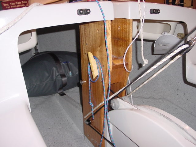 The Flying Scot, being of a classic sailboat design, comes standard with a hand bailer seen hanging from the starboard storage bin.  The boom vang bridle system is shown as the white line passing through the turning block and attached to the base of the stanchion.  The black line running to the base of the stanching and then aft is the boom vang control line.