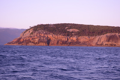 Past Cape Wellington; brown and orange rocks in the sunrise, of Brown Head.