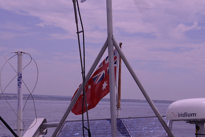 Our Australian flag, as Melbourne recedes.  Note solar panel, and iridium phone. Central tripod support wind generator.