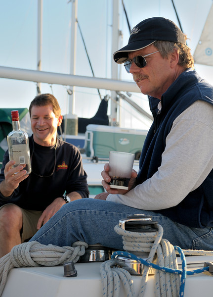 """Commodore (R)  finishes a bottle of Mount Gay on """"Gay Force."""" Dave Lach of """"Legacy"""" smiles approvingly."""