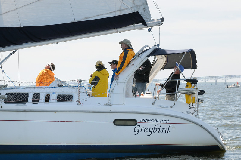 "Captain Keith Altmiller at the helm of ""Greybird"" checks sail trim."
