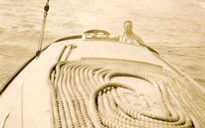 """Dad sailing the """"Haerere"""".  Note warp on cabin top, as foredeck space may have been limited; Dad liked to have plenty of warp. Did Mum take the picture?"""