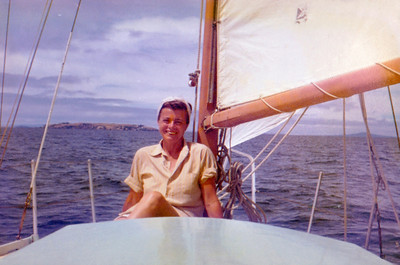 "A lovely photo of Mum, the time we hired a small displacement sloop and sailed out to the Great Barrier Island.  Here with Rangitoto to starboard and probably Tiri Tiri Matagi or Rakino to port, most likely we are sailing back from a stopover at Kawau Island.  I have this photo of Mum framed at my beach house ""Here Hau""."