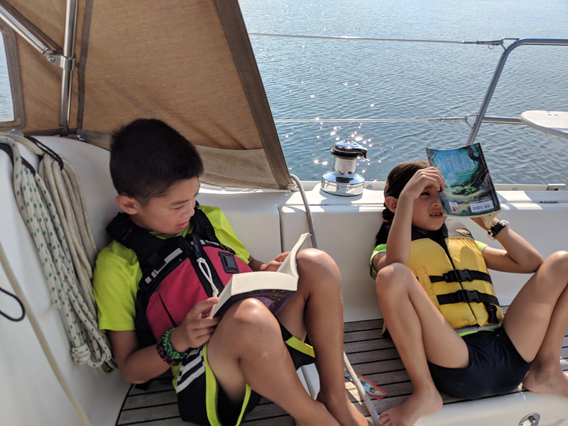 Kids doing some reading. The next day there was no wind. We motored across to Michigan Island to explore ashore.