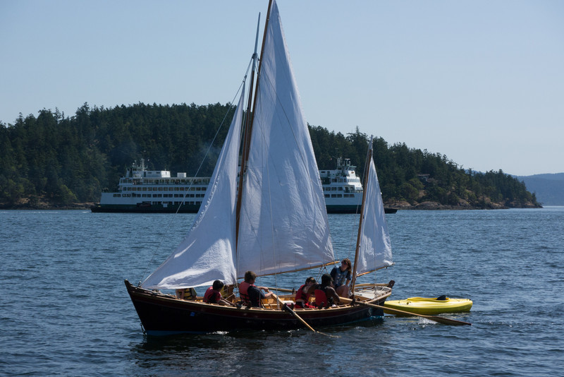 A tiny yawl that was being rowed, sails luffing, pulling a kayak