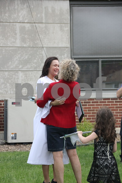 (Left to right) Madison Julius shares a  congradulatory hug with a loved one after Saint Edmonds graduation ceremony held on May 17, 2015