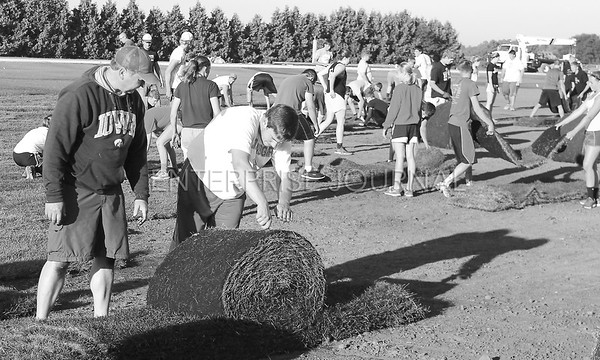 A big group of helpers came out to the new football field to help with laying sod on the new field on Thursday, July 23, 2015 in St. Ansgar, Iowa. (EJ Photo/ Angie Hansen)