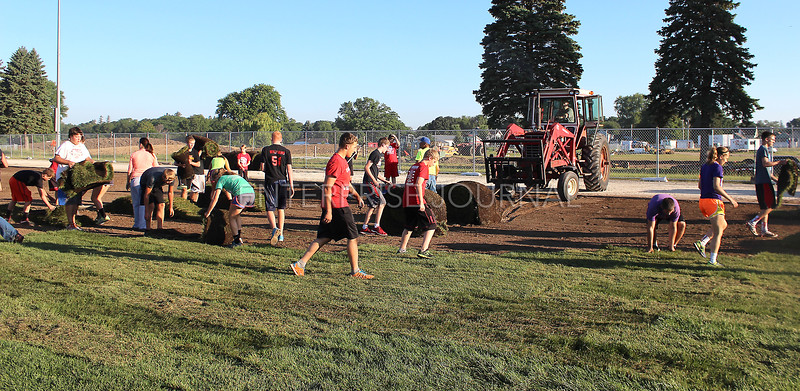 Volunteer workers help lay sod on the new football field as the tractor brings in more sod to be laid. (EJ Photo/ Angie Hansen)