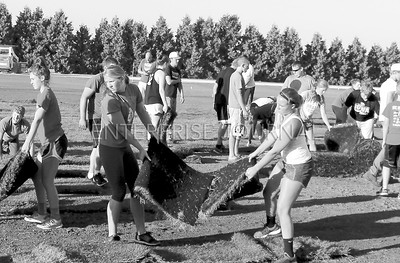 Left, Daria Jorgensen and Right, Tara Kramer are hard at work helping along with a big crew with laying of the sod on the new football field. (EJ Photo/ Angie Hansen)