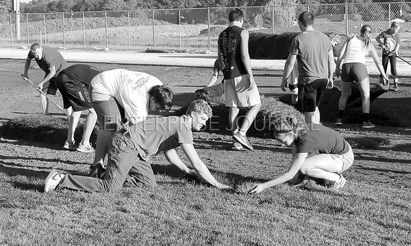 Ethan Mayer (left) and Kelsie Willert (right) were some of the students on hand to help lay sod on the new football field on Thursday, July 23, 2015. (EJ Photo/ Angie Hansen)