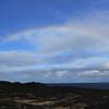 Faint arching rainbow over lava rock in hawaii