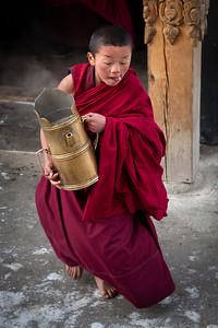 Young monk bringing tea