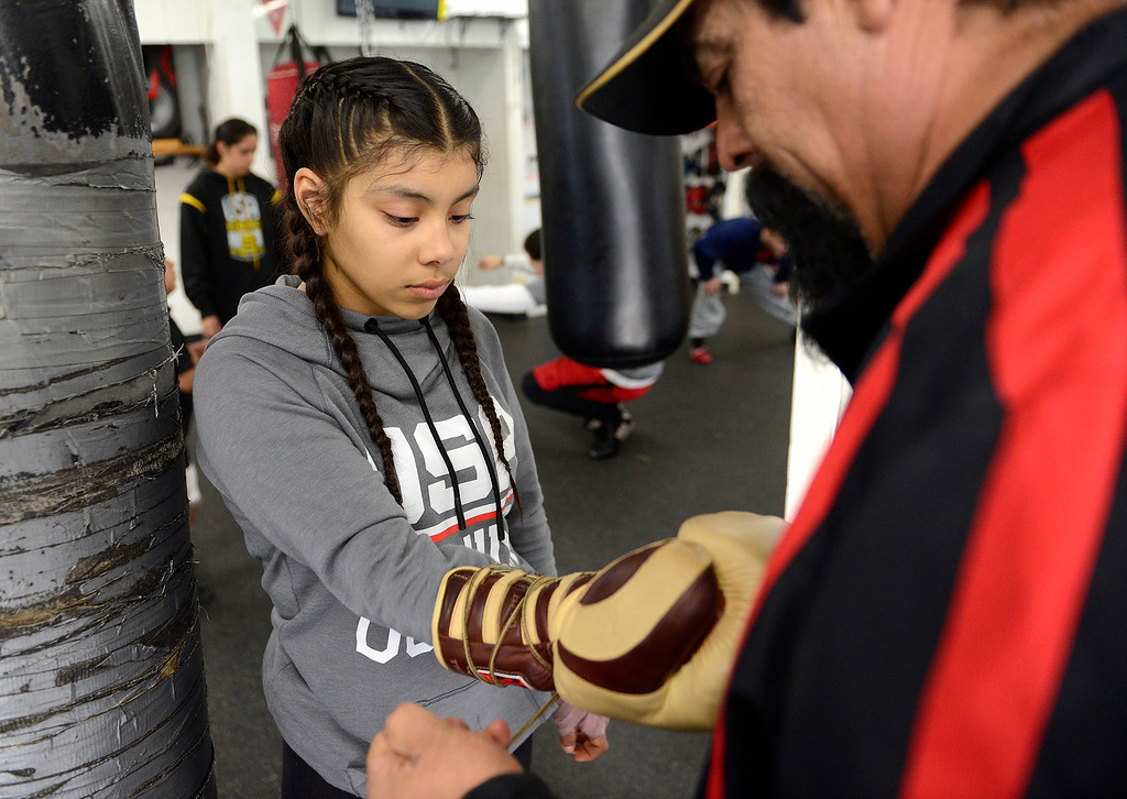 . Salinas Boxing Club fighter Maria Jardines, 14, gets help with her gloves from boxing coach Robert Medrano at the Salinas Boxing Club on Thursday, March 22, 2018.  (Vern Fisher - Monterey Herald)