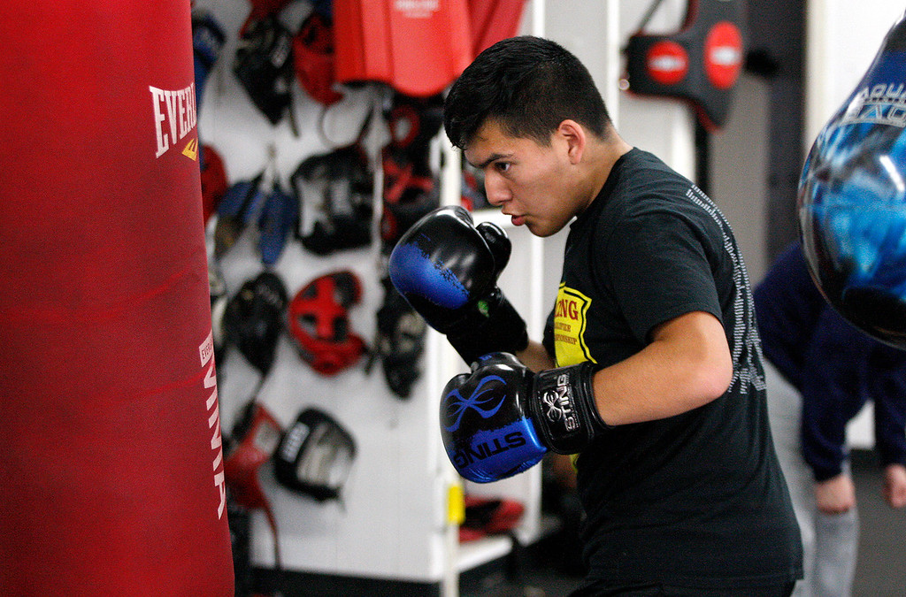 . Salinas Boxing Club fighter Jose Picazo, 12, hits the heavy bag during training at the Salinas Boxing Club on Thursday, March 22, 2018.  (Vern Fisher - Monterey Herald)