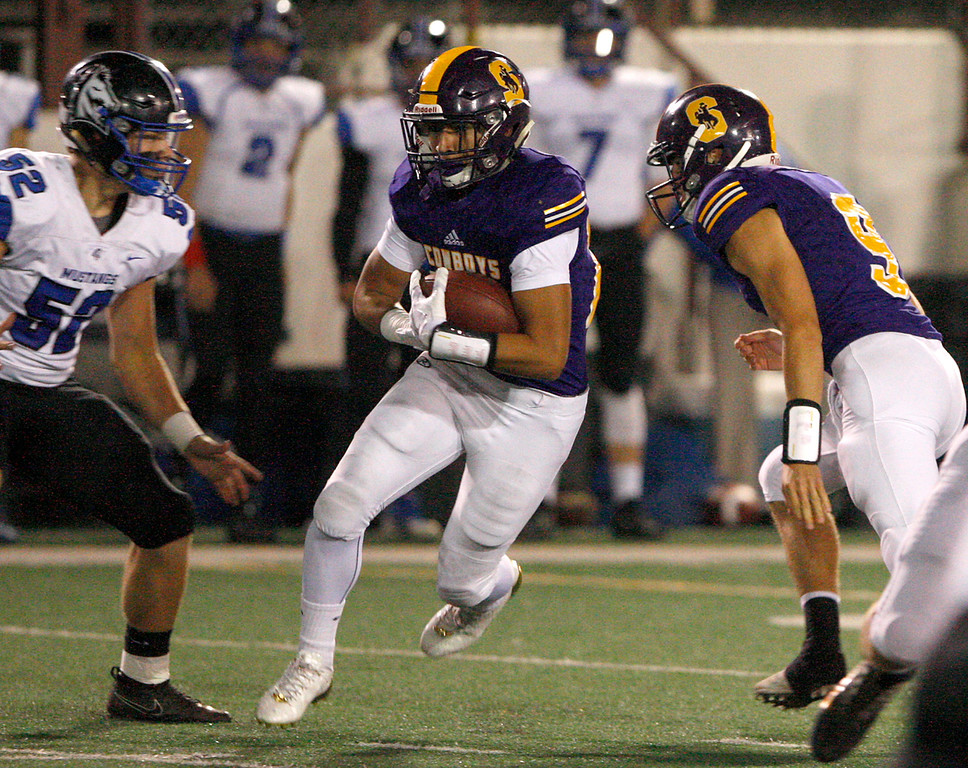 . Salinas High running back Richard Cerda (24) runs between Monte Vista Christian defender Cory Margo (52) and teammate Brett Reade (9) during the first half of their game in Salinas on Friday, Oct. 20, 2017.  (Vern Fisher - Monterey Herald)