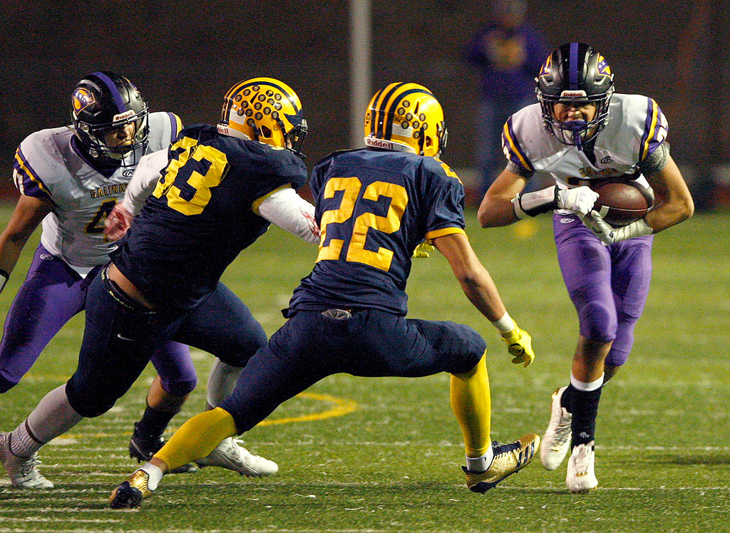 . Salinas High\'s Zachary Robison (22) tries to elude Milpitas High defenders Faiven Papalii (32) and Tai Nguyen (22) in the first half of their Central Coast Section Open Division I championship football game in San Jose on Friday, December 1, 2017.  Salinas High won the championship 25-18.  (Vern Fisher - Monterey Herald)