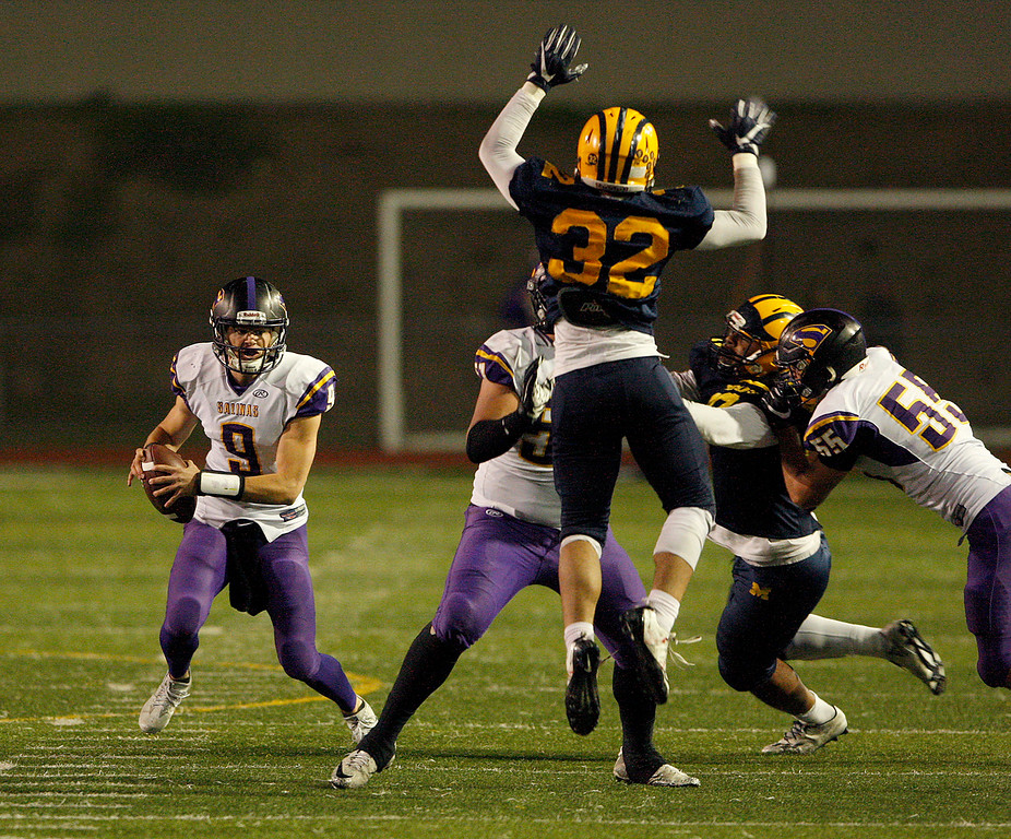 . Salinas High\'s Brett Reade (9) scrambles with the ball away from Milpitas High defender Faiven Papalii (32) in the first half of their Central Coast Section Open Division I championship football game in San Jose on Friday, December 1, 2017.  (Vern Fisher - Monterey Herald)