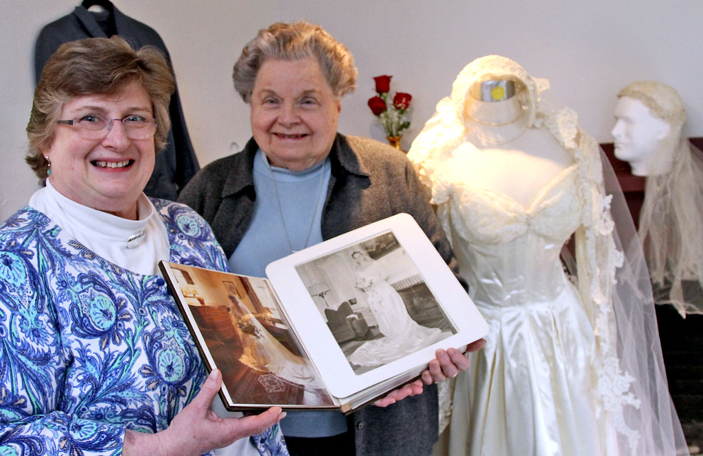. Linda Prescott on left , along with her mother Dolores Rawding, hold two different photos of them in the same wedding dress, Linda from 1978 and Dolores from 1952, and the same dress is on the right. SUN/David H. Brow