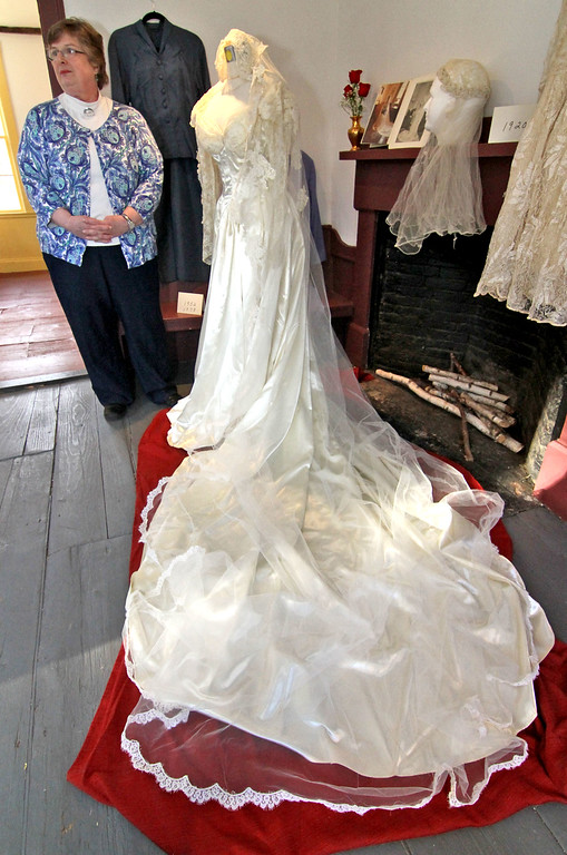 . Chelmsford resident Linda Prescott stands next to the wedding dress that was hers in 1978 and her mothers in 1952, on display at the Garrison House. SUN/David H. Brow