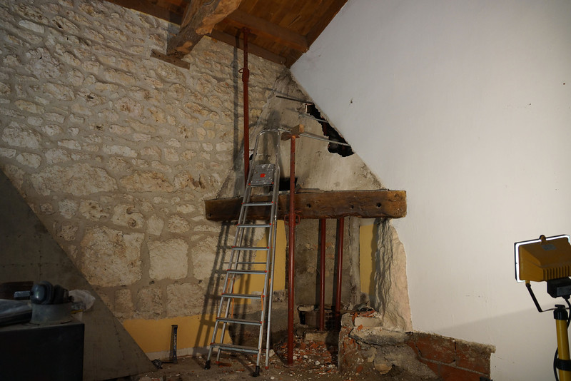 Carefully removing the old fireplace installation.  The mantel will be moved to form a lintel.