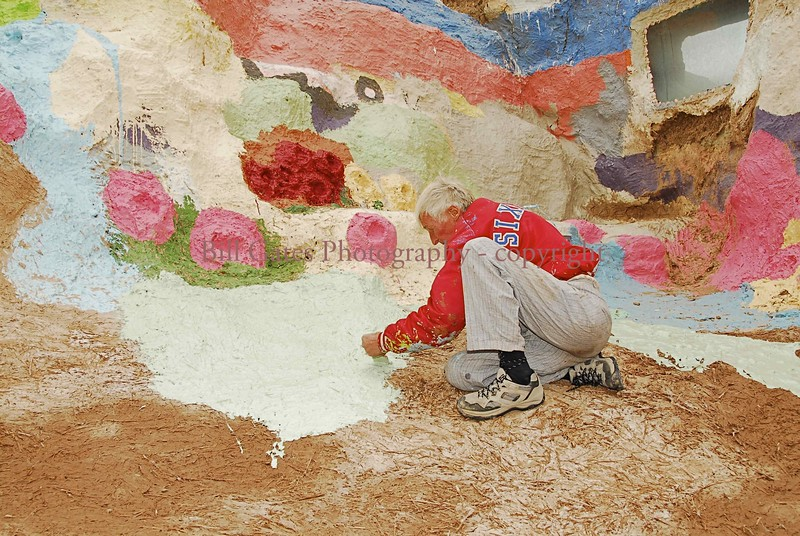 Leonard Knight paints on a surface of adobe mud