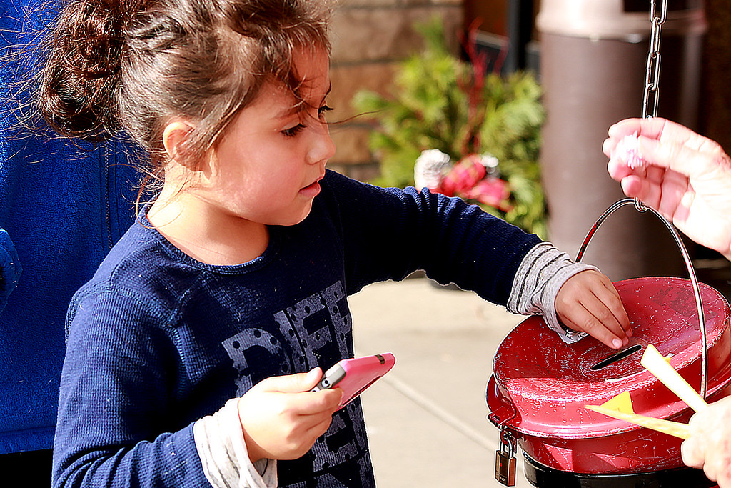 . Jalizah Madeino, 7, gives a donation to The Salvation Army bellringers at the Orchard King Soopers on Dec. 1, 2018 in Loveland, Colo.Photo by Taelyn Livingston/ Loveland Reporter-Herald