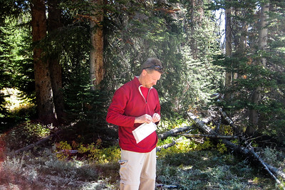 When we arrive at base camp, we unload for the climb. I consult the map and appear to be a little pensive as we prepare to go on up.  [Terry Patterson photo]