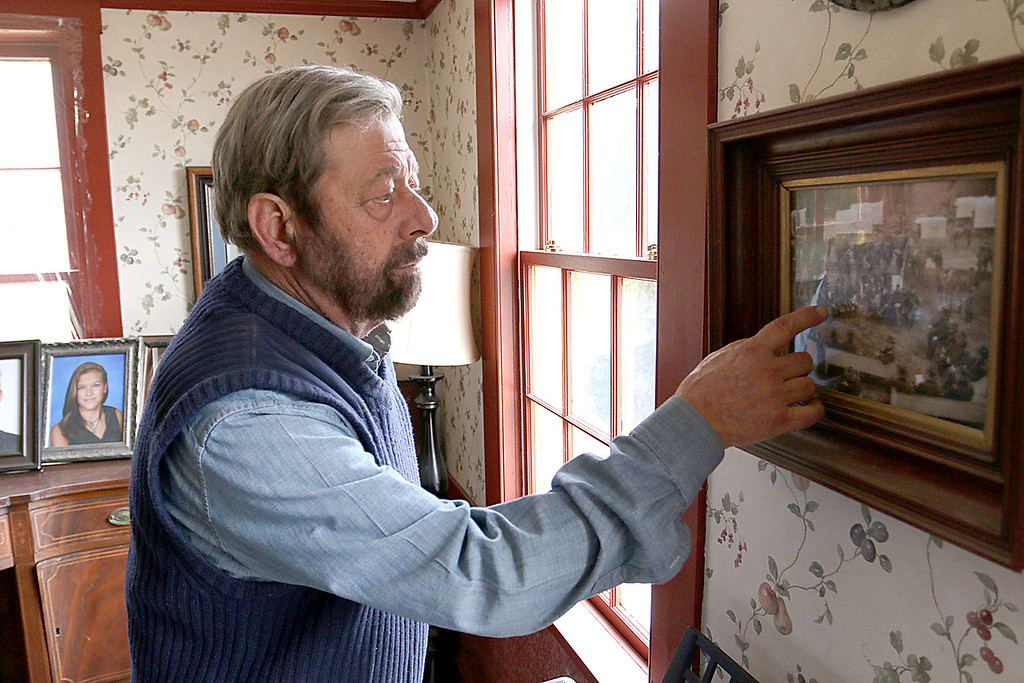 . Sam Grant, who re-enact Gen. Ulysses S. Grant, points to a picture he is in while playing the former president that sits on his wall at his home in Townsend MA. It was a pictures taken to look like an old picture. SENTINEL & ENTERPRISE/JOHN LOVE