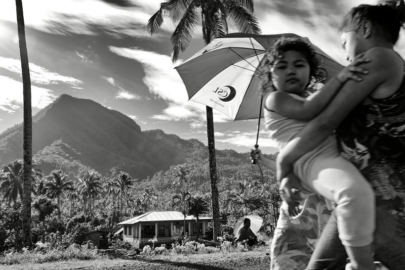 Jeune femme portant son enfant sur la route à Falevao. Ile d'Upolu/Archipel des Samoa