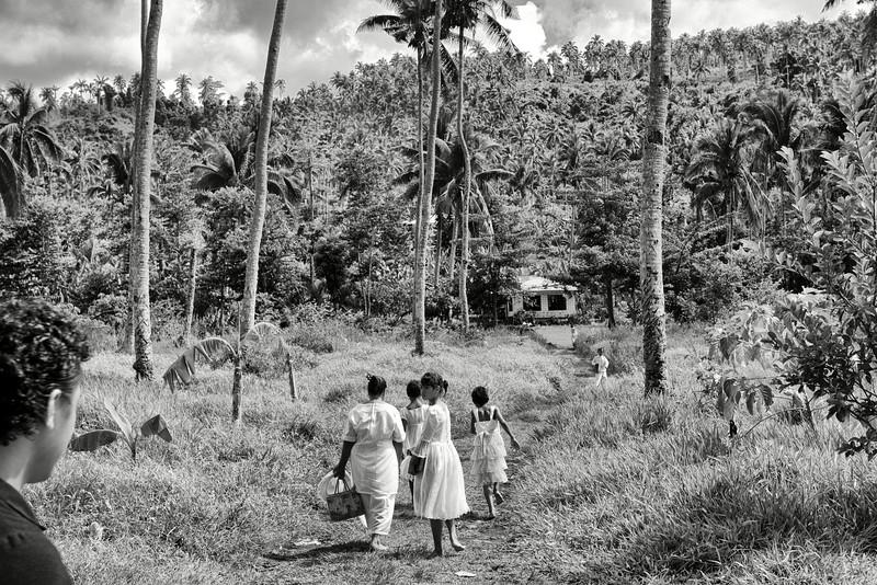Une jeune fille laissant son ami derrière elle après la messe dominicale de l'église de Saanapu-uta. Ile d'Upolu/Archipel des Samoa