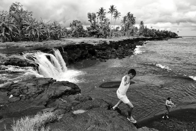 Un enfant jouant au bord des chutes de Mu Pagoa. Ile de Savaii/Archipel des Samoa