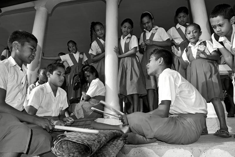 Groupe d'écoliers d'Auala jouant des percussions sur une natte à l'extérieur de leur salle de classe. Ile de Savaii/Archipel des Samoa