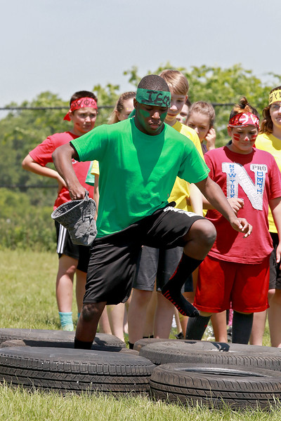 Samoset Middle School seventh graders held a Greek Olympics at the school on Tuesday morning with eight teams. Running a tire course is seventh grader Jean Ronald. SENTINEL & ENTERPRISE/JOHN LOVE
