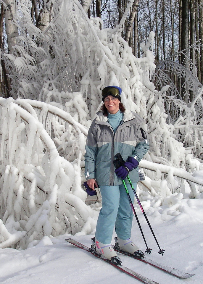 Kristin Hand takes a break from skiing to pose beside ice-crusted branches.