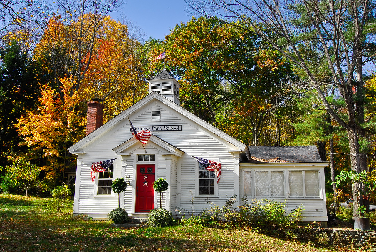 Jenness Pond School, circa 1793, with American flags and patriotic buntings, surrounded by fall color, Northwood, NH.