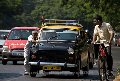 Driver pushing his broken down taxi on the streets of Bombay