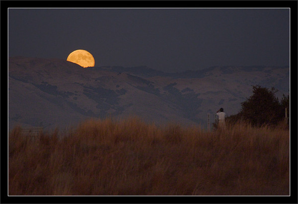 Tweet the Moon<br /> <br /> The fall Harvest Moon rises<br /> over the East Bay mountains.<br /> <br /> A man stops on his walk to watch the moonrise<br /> and take a photo with his phone.<br /> <br /> East Bay Mountains: Diablo Range<br /> San Francisco Bay Area, California<br /> <br /> 30-SEP-2012