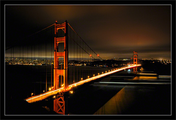 Over and Under the Golden Gate<br /> <br /> Automobiles and marine vessels pass<br /> through the Golden Gate Bridge<br /> on a very busy Saturday night.<br /> <br /> (SF is visible in the distance<br /> under the marine-layer clouds.)<br /> <br /> City of San Francisco & Marin County,<br /> California<br /> <br /> 11-JUN-2011
