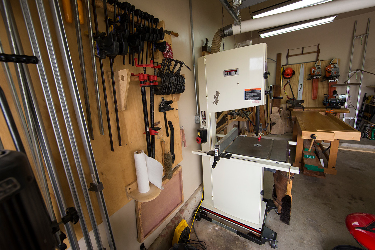 "Here is one of the two massive machines I own—the 3HP 18"" bandsaw. Years ago I owned a massive table saw, and it was great. But it was too big and heavy to move comfortably, and it took up virtually the entire shop. I remember reading a Fine Woodworking article arguing the virtues of a large band saw in favor of a large table saw when space is at a premium. I was very skeptical at first, but I've found it to be a a perfectly viable solution. Band saws are amazing. They're accurate, safe (WAY safer than a table saw), take up a minimum of floor space, and you can cut curves with them. You can also resaw stock safely and without a bunch of waste. I may or may not have stood in my shop staring at my band saw when no one else was around. You can't prove anything."