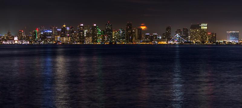 Orange-colored Bull Moon rises among San Diego skyline